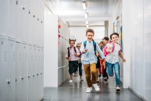 Kids running through school hall changing class