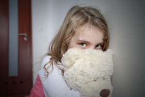 Young sad girl huging a teddy bear hoping for change