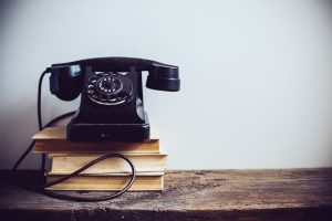 change comes with a Black vintage rotary phone and books on rustic wooden table, on a white wall background